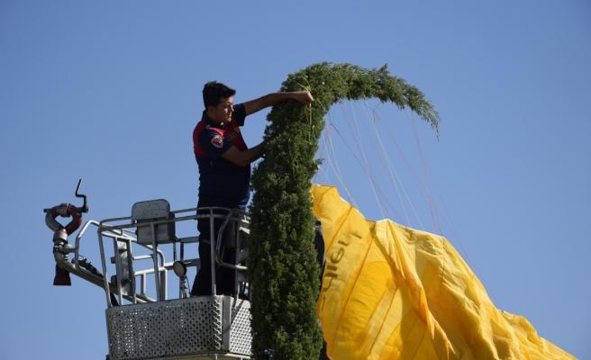 Yer çalışması yapan paraşütçü rüzgar çıkınca çam ağacına takıldı